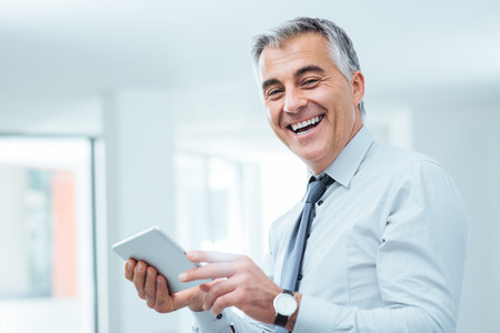 Smiling confident businessman looking at camera and using a digital touch screen tablet Stock Photo