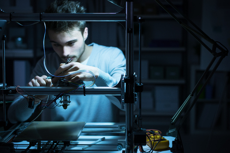 Young engineer working at night in the lab, he is adjusting a 3D printer's components, technology and engineering concept