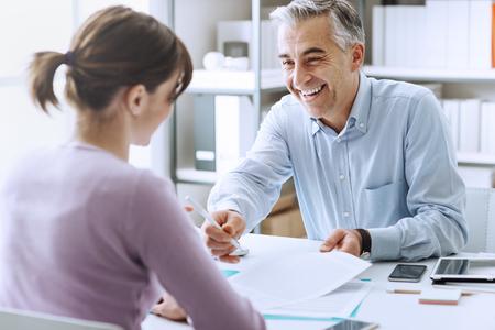empleados trabajando: mujer joven que tiene una reuni�n de negocios y firmar un contrato de concepto, el reclutamiento y el acuerdo