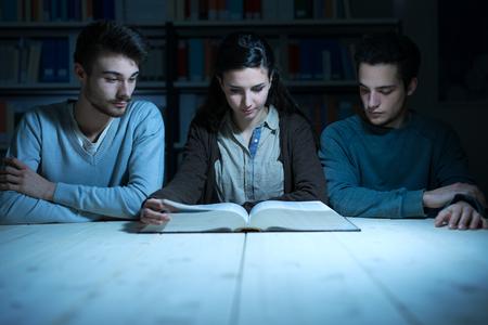 personas leyendo: estudiantes universitarios jóvenes que leen un libro junto a altas horas de la noche, el conocimiento y el aprendizaje de conceptos