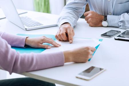 De jonge vrouw die een commerciële vergadering met een stafmedewerker in zijn bureau heeft, richt op een contract en geeft verklaringen