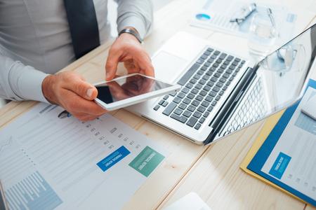 テクノロジー: デスクで働いて、タッチ画面のタブレット、技術およびコミュニケーションの概念を使用してプロのビジネスマン