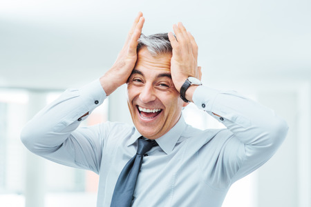 adult oops: Cheerful careless businessman laughing and touching his forehead