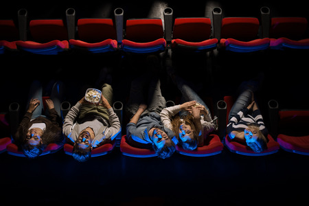 people watching: Young happy people in the movie theater having fun, they are looking up and eating popcorn, top view, entertainment and leisure concept