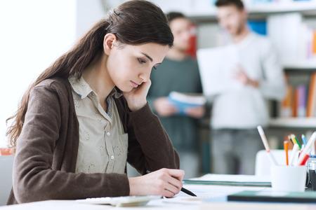 deberes: Hembra joven estudiante hacer la tarea y estudiar en la biblioteca, los estudiantes y los estantes en el fondo, la educación y el aprendizaje de conceptos