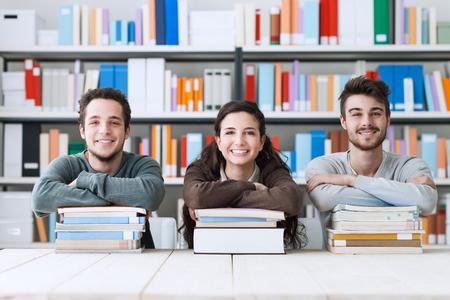 Fiatal egyetemisták a könyvtárban tanul együtt, ők mosolyogva fényképezőgép, támaszkodva egy halom könyvet