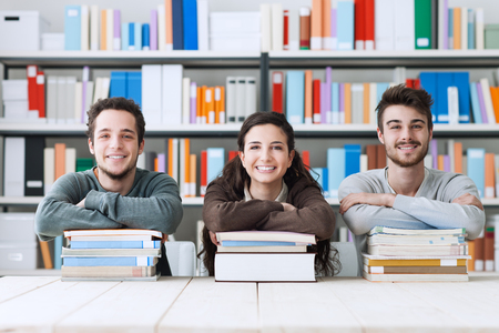 college: Young college students at the library studying together, they are smiling at camera and leaning on a pile of books
