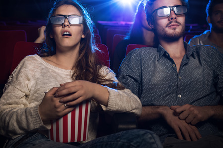 Young teenagers at the cinema wearing glasses and watching a 3d movie, a girl is eating popcorn, entertainment and movies concept