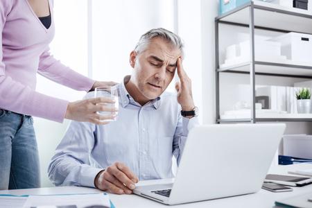 Vermoeide zakenman in het kantoor werken op het bureau en het hebben van een slechte hoofdpijn, zijn collega geeft hem een glas water en zijn schouder aan te raken Stockfoto