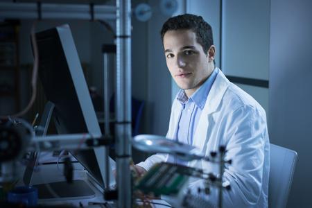 bata de laboratorio: joven investigador en el laboratorio, que llevaba una bata de laboratorio y trabajando con un ordenador, una impresora 3D en primer plano, que está mirando a la cámara
