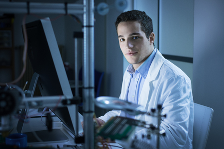 engineering tools: Young researcher in the lab, wearing a lab coat and working with a computer, 3D printer on foreground, he is looking at camera Stock Photo