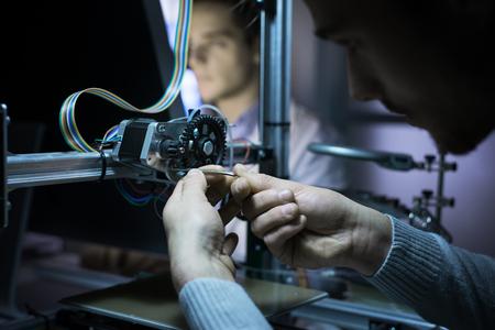 Mladý inženýr v laboratoři pracuje na 3D tiskárně, další student pracuje s počítačem na pozadí, inovacích a technické koncepce