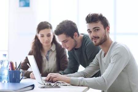Groupe d'étudiants de niveau collégial à la réception en utilisant un ordinateur portable, la mise en réseau et étudier ensemble, l'éducation et le concept d'apprentissage