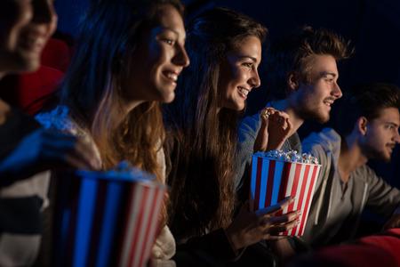Grupo de amigos adolescentes en el cine viendo una película juntos y comiendo palomitas de maíz, el entretenimiento y el disfrute concepto
