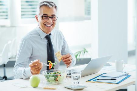 사무실 책상에 앉아 점심 시간을 가진 사업가 웃고, 그는 샐러드 그릇을 먹고있다 스톡 콘텐츠