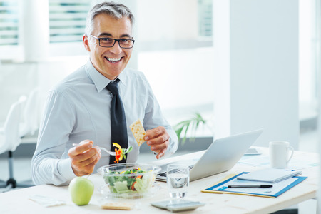 Smiling businessman sitting at office desk and having a lunch break, he is eating a salad bowl Standard-Bild