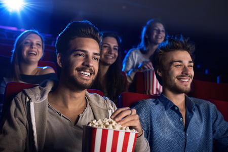adolescent: Young people sitting at the cinema, watching a movie and eating popcorn, two smiling men on foreground
