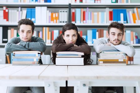 jovenes estudiantes: Jóvenes estudiantes universitarios en la biblioteca estudiando juntos, se apoyan en un montón de libros y mirando a la cámara