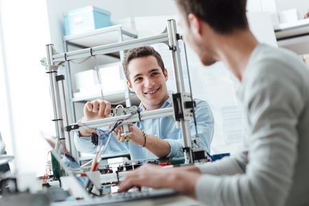 ingenieria elÉctrica: Los estudiantes de ingeniería que trabajan en el laboratorio, un estudiante está ajustando los componentes de una impresora 3D, el otro en primer plano está utilizando una computadora portátil