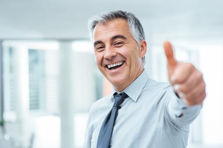 Vrolijke zakenman thumbs up poseren en glimlachen op camera Stockfoto