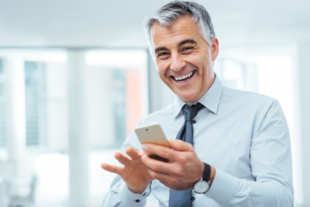 mobile internet: Smiling cheerful businessman using a touch screen smart phone and looking at camera Stock Photo
