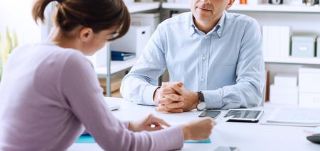 recursos humanos: hombre de negocios maduro y una mujer joven que tiene una reunión de negocios en la oficina, que están discutiendo juntos