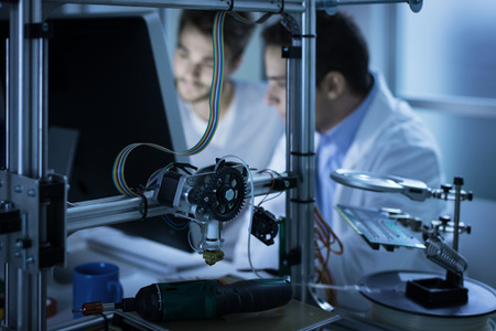 Fiatal dolgozó mérnökök a laboratóriumban, és a számítógép segítségével, 3D-s nyomtató előtér, a tudomány és a technológia fogalmát