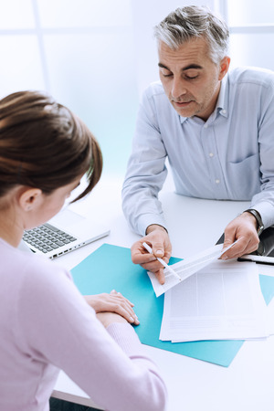 explanations: Young woman meeting a professional consultant in his office, he is holding a document and giving explanations Stock Photo