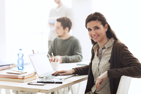 camera girl: College students in the class, a girl is smiling at camera and using a laptop on foreground Stock Photo