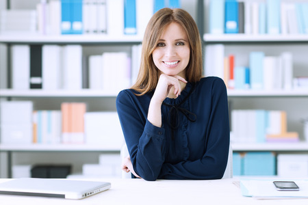 attractive female: Confident beautiful businesswoman sitting at desk and posing, she is smiling at camera, office shelves on background Stock Photo