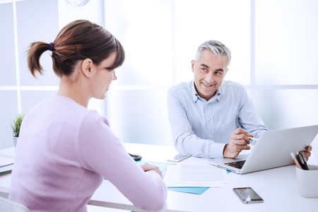 Friendly funny businessman having a meeting with a woman in his office, he is smiling at her and flirting