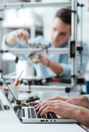 Les élèves ingénieurs travaillant dans le laboratoire, un étudiant ajuste les composants d'une imprimante 3D, l'autre sur le premier plan est d'utiliser un ordinateur portable Banque d'images