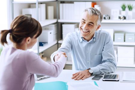 Heureuse jeune candidate serrant la main de son employeur après un entretien d'embauche, un emploi et un concept de réunions d'affaires
