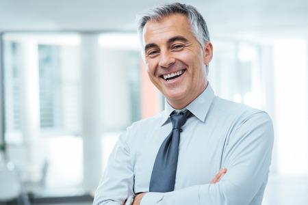 Succesvolle zakenman stellen met gekruiste armen en glimlachen op camera Stockfoto