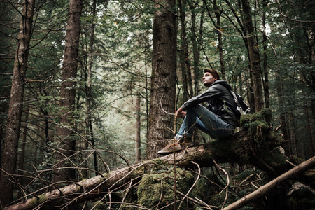 Young man sitting on a trunk in the forest and relaxing, freedom and individuality concept Stock Photo