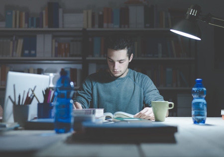 Teenage student reading books and studying late at night, learning and education concept Stock Photo