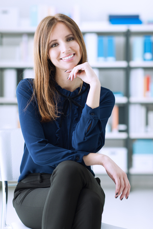 women legs: Confident businesswoman posing in the office, she is sitting on a chair and smiling at camera