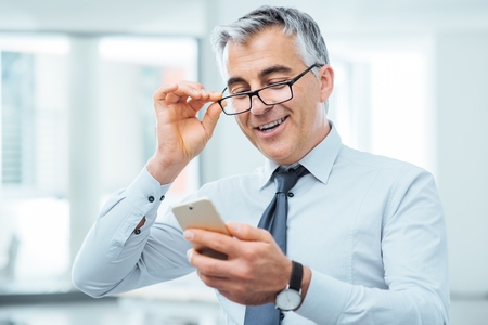 reading: Smiling businessman with eyesight problems, he is adjusting his glasses and reading something on his mobile phone Stock Photo