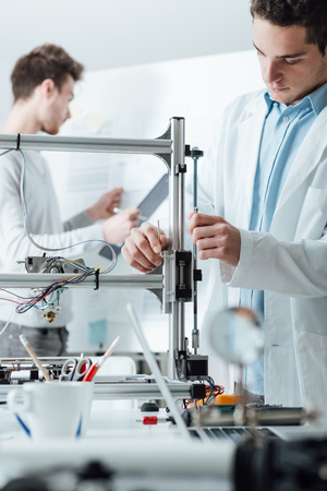mechanical men: Mechanical engineers working in the laboratory, they are using an innovative 3D printer, prototyping and technology concept
