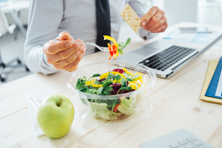 working attire: Businessman having a lunch break at desk, he is eating fresh salad and holding a cracker, unrecognizable person