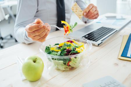 Geschäftsmann mit einer Mittagspause am Schreibtisch, er isst frischen Salat und hält einen Cracker, Nicht erkennbare Person