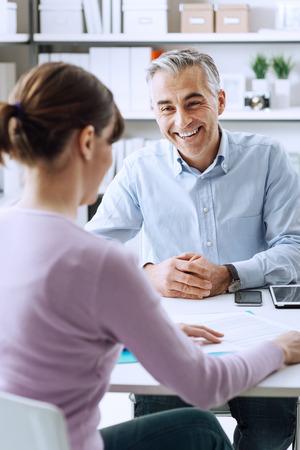 성숙한 사업가 및 사무실에서 비즈니스 미팅 데 젊은 여자, 그들은 함께 논의하고있다