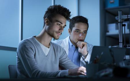 hombres trabajando: Los estudiantes que trabajan por la noche en el laboratorio, que están usando un ordenador portátil, trabajo en equipo y el concepto de la educación