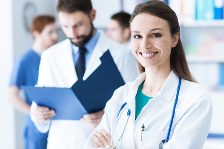 medical records: Confident doctor checking medical records on a clipboard, a female doctor is smiling on foreground, healthcare concept Stock Photo