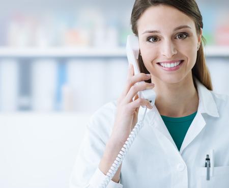 受話器を持って電話に答えて笑顔の女性医師の医療サービス 写真素材