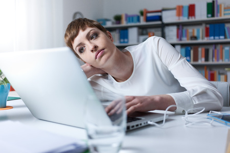 woman in office: Tired woman in the office leaning on her hand an using a laptop Stock Photo