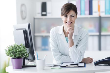 턱에 손을 병원 리셉션 데스크에 기대어 매력적인 젊은 여성 의사, 그녀는 카메라, 의료진 및 건강 관리 개념에 미소 스톡 콘텐츠