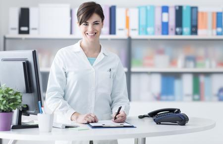 젊은 여성 의사 클리닉 리셉션에서 일하고 웃 고, 그녀는 컴퓨터를 사용 하 고 의료 보고서 작성