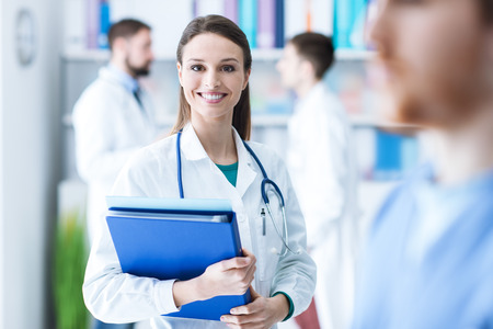 pathologist: Confident attractive female doctor in the office holding medical records and folders, she is smiling at camera, medical staff on the background