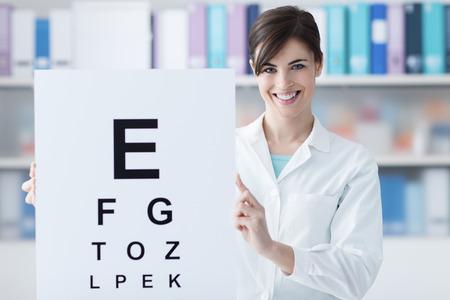 oculista: oculista profesional femenina que sostiene una carta de ojo y sonriendo a la cámara, el examen médico y el cuidado de los ojos concepto